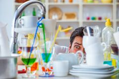 The man frustrated at having to wash dishes. Man frustrated at having to wash dishes Royalty Free Stock Image