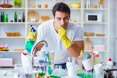 The man frustrated at having to wash dishes Stock Photo
