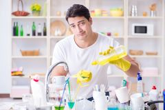 The man frustrated at having to wash dishes. Man frustrated at having to wash dishes Royalty Free Stock Photography