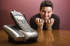 Frustrated waiting for the phone to ring. A man is frustrated waiting for the phone Royalty Free Stock Photography
