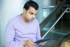 Man frustrated by what he sees on tablet Stock Image