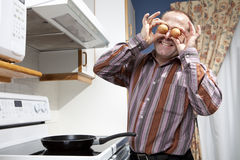 Man frying eggs Royalty Free Stock Images