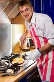 Man frying eggs Stock Photography