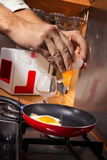 Man frying eggs Royalty Free Stock Image