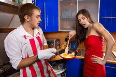 Man frying eggs for his girlfriend Royalty Free Stock Image
