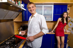Man frying eggs for his girlfriend Stock Photography