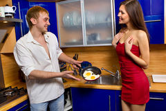 Man frying eggs for his girlfriend Stock Image