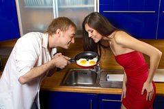 Man frying eggs for his girlfriend Royalty Free Stock Images