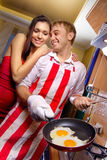 Man frying eggs for his girlfriend Royalty Free Stock Photography