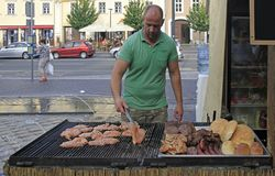 Man is frying meat at open-air festival in Sopron, Hungary. Sopron, Hungary - May 28, 2018: man is frying meat at open-air festival in Sopron, Hungary royalty free stock image