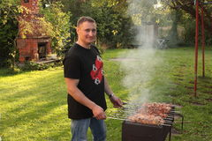 Man is frying meet in garden. Food on skewer, grill, barbecue Stock Photo