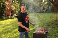 Man is frying meet in garden. Food on skewer, grill, barbecue Royalty Free Stock Images