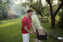 Man is frying meet in garden. Food, skewer, grill, barbecue Stock Image