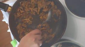 A man is frying mushrooms in a frying pan. Removes the lid, stirs the mushrooms. A man is frying mushrooms in a frying pan. Removes the lid, stirs the mushrooms stock video