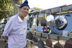 A man with frying pans, Mississippi. A man stood next to frying pans hanging on wooden rails, Mississippi Stock Photo