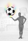 Man in full body suit holdig soccer ball Stock Photos