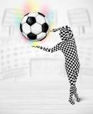 Man in full body suit holdig soccer ball Stock Images