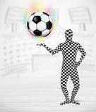 Man in full body suit holdig soccer ball Stock Photo