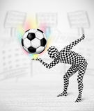Man in full body suit holdig soccer ball Royalty Free Stock Image