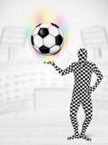 Man in full body suit holdig soccer ball Stock Image