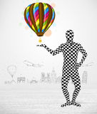 Man in full body suit holding balloon Stock Photo