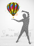 Man in full body suit holding balloon Stock Photography