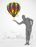 Man in full body suit holding balloon Stock Image