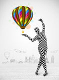 Man in full body suit holding balloon Royalty Free Stock Images