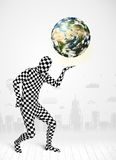 Man in full body suit holding planet earth Royalty Free Stock Image
