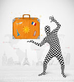 Man in full body suit presenting vacation suitcase Stock Images