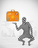 man in full body suit presenting vacation suitcase, tourist attractions in background Royalty Free Stock Image