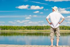 Man in full length with bare feet on a wooden pier on the background of a beautiful lake royalty free stock photography