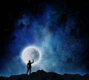 Man and full moon . Mixed media. Silhouette of man against starry sky with big full moon Stock Image