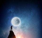 Man and full moon . Mixed media. Silhouette of man against starry sky with big full moon Stock Photos