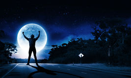 Man and full moon. Young screaming man at night with big full moon at background Royalty Free Stock Images