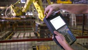 Man fungerande robotic utrustning med fjärrkontroll på den industriella fabriken, växt arkivfilmer