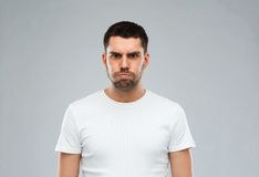 Man with funny angry face over gray background Stock Image