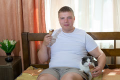 Man and funny cat eating ice cream cone in the bed Royalty Free Stock Photos