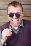 Man with funny sunglasses on a stick poses face Royalty Free Stock Photography