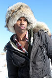 Man with Fur Cap. A black men in a fur cap and a winter parka against a clear blue sky Stock Photography