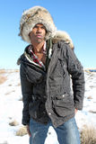 Man with Fur Cap. A black man in a fur cap and a winter parka stands in the snow against a clear blue sky Royalty Free Stock Photos