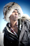 Man with Fur Cap. A black man in a fur cap and a winter parka against a clear blue sky Royalty Free Stock Image