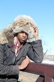 Man with Fur Cap. A black man in a fur cap and a winter parka leans against a bridge rail Stock Images