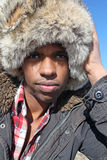 Man with Fur Cap. A black man in a fur cap and a winter parka against a clear blue sky Stock Photography