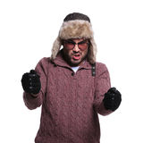 Man in fur hat and leather gloves is driving an imaginary race c. Young man in fur hat and leather gloves is driving an imaginary race car on white background Stock Photos
