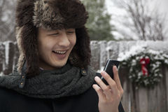 Man in Fur Hat Looking at Cell Phone Royalty Free Stock Image