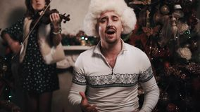 Man in fur hat singing with string quartet sitting in room near christmas tree. Unshaved caucasian joyful man in white fur hat singing with string quartet stock video footage