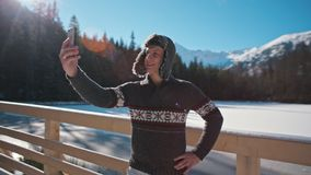 Man in Fur Hat is Taking Selfie by SmartPhone with Mountains and Lense Flare. Handsome Man in Fur Hat is Taking Selfie by SmartPhone Outdoors with Beautiful stock video footage