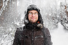 Man in fur winter hat with ear flaps smiling. Portrait Stock Photos