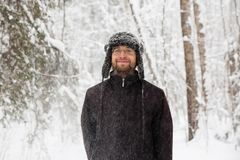 Man in fur winter hat with ear flaps smiling portrait. Extreme in the forest Stock Photo